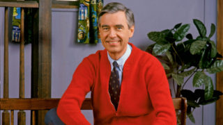 Mister Rogers in a red cardigan and tie on set