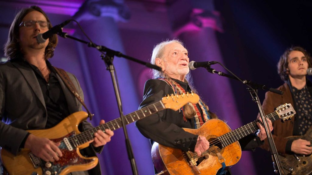 Willie Nelson singing on stage with a guitar