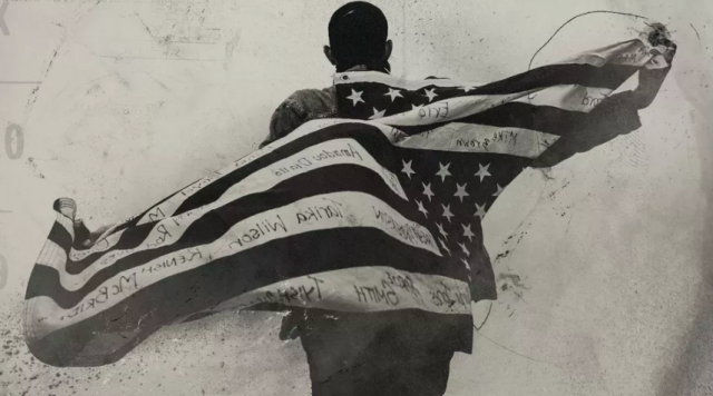 Image of man with American Flag draped across his back